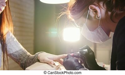 Professional nails care in process, cosmetician with mask in black gloves making nails female customer for a manicure with gel cover, slider