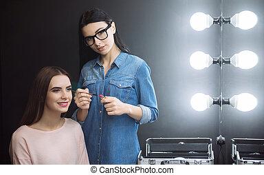Professional nice makeup artist holding a lipstick