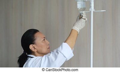Professional nurse adjusting a dropper - Make it sterile....