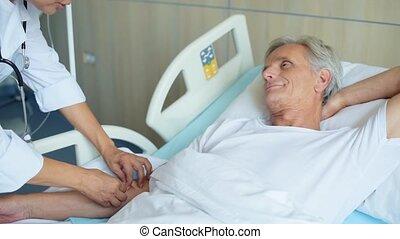 Professional nurse getting an aged man on a drip