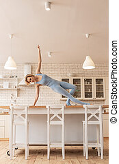 Unusual skinny young performer dancing on kitchen table -...