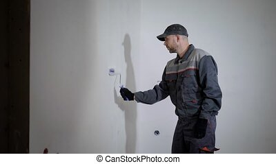 professional painter is wearing working uniform and cap is...
