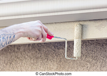 Professional Painter Using Small Roller to Paint House Fascia