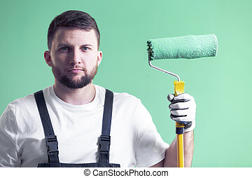 Professional painter with roller against green wall in interior