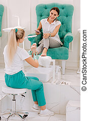 Professional pedicure master working hard in beauty salon
