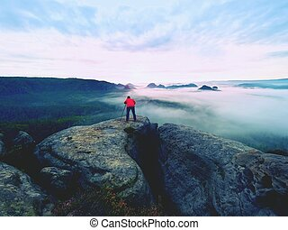 Professional photographer above clouds. Man takes photos with camera on tripod on rocky peak.