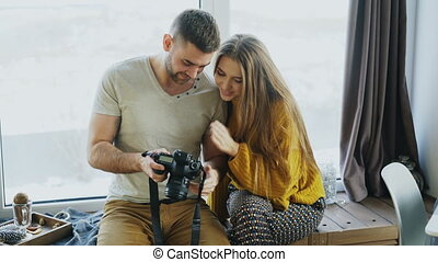 Professional photographer man showing photos on digital camera to student girl at personal materclass in photo studio indoors