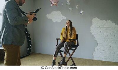 Professional photographer man taking photo of beautiful model girl with digital camera in studio