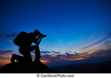 professional photographer silhouette at sunset or sunrise - ...