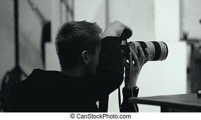 photographer takes a digital camera in a photo studio -...