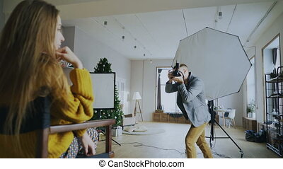 Professional photographer taking photos of model on digital...