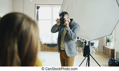 Professional photographer taking photos of model on digital...