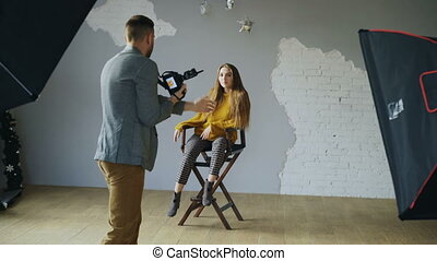 Professional photographer taking photos of model on digital camera working in photo studio