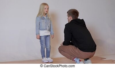 photographer talking to a cute little model girl at a photo...