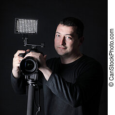 professional photographer with camera on tripod. isolated on black background