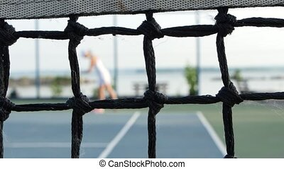 Professional player expecting the tennis ball on court, net in front. Dolly shot