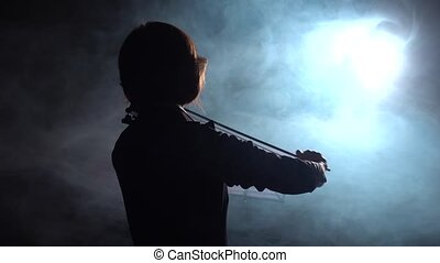 Professional playing the violin in a dark studio with a...