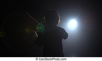 Professional playing the violin in a dark studio with a lantern from it glare. Black smoke background. Back view