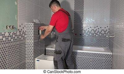 Professional plumber man flush water from tube of toilet flushing mechanism. Worker install toilet flush button in new modern bathroom. Static shot.