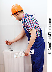 Professional plumber repairing white radiator