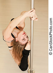 Professional pole dance woman sitting on the floor