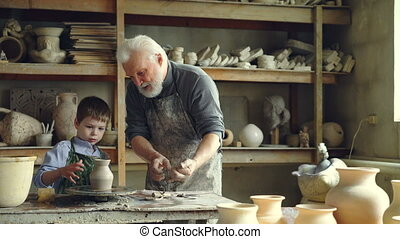 Professional potter is cutting ceramic pot from throwing...