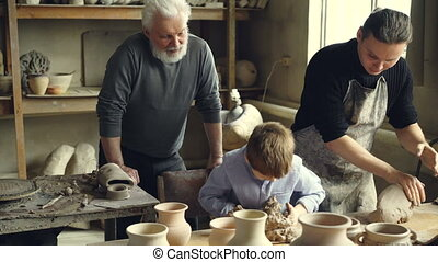 Professional potter is kneading clay on worktable in home...