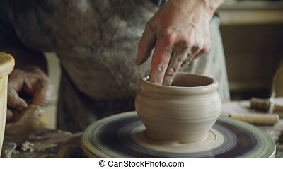 Professional potter is making clayware on potter's wheel, looking at half-finished pot and checking quality of work. Traditional occupation and creating ceramics concept.