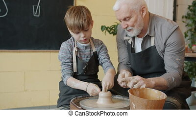 Professional potter senior man is teaching little boy to make ceramic vase on throwing wheel in studio working together wearing dirty aprons.