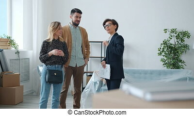 Professional realtor is talking to customers man and woman showing new apartment discussing deal together. People and accommodation business concept.