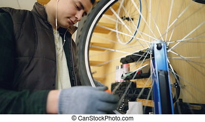 Professional repairman is fixing bicycle wheel spokes straightening them with special tools and rotating wheel to check spokes. Occupation and repair concept.