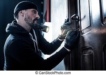 Unlocking. Serious professional bearded robber holding a torch and wearing gloves and unlocking the door
