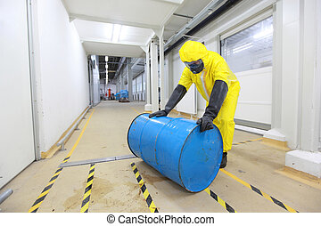 fully protected in yellow uniform, mask, and rubber gloves and boots worker, rolling the barrel with toxic substance