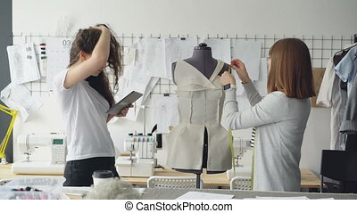 Professional seamstress is measuring patterns on mannequin...