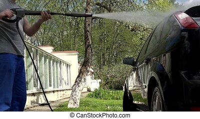Professional service man with high pressure water jet washing car.