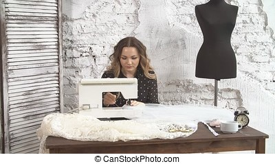 Professional sewing machine in small business studio with female tailor working on new dress.