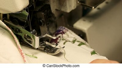 Professional sewing machine overlock with white fabric close-up
