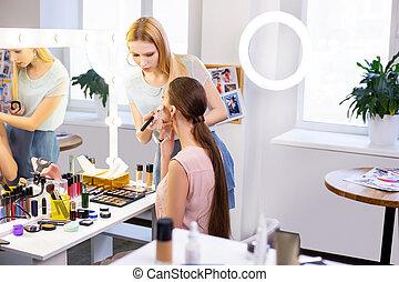 Professional skilled female visagiste putting on makeup