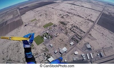 Professional skydiver fly on parachute in blue sky over sandy Arizona. Sunny day