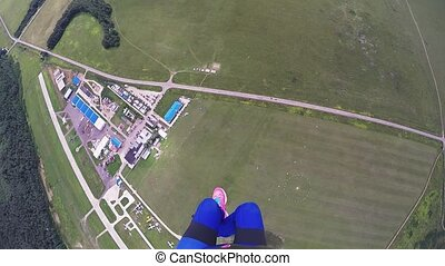 Professional skydiver girl parachuting, fly above green...