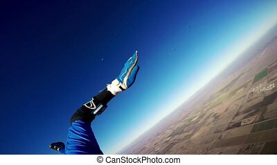 Professional skydiver open parachute in blue sky fly above Arizona. Sunny day.