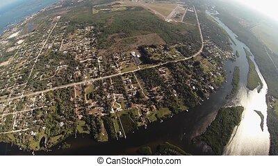 Professional skydiver parachuting above flatland. Landscape....