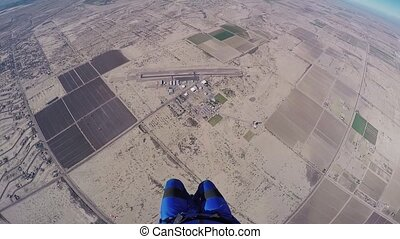 Professional skydiver parachuting in blue sky above Arizona....