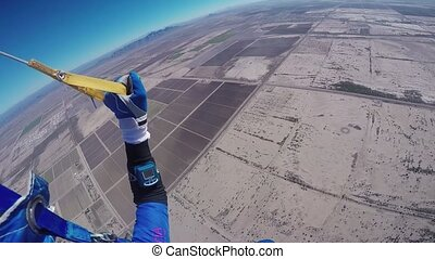 Professional skydiver parachuting in sky above Arizona....