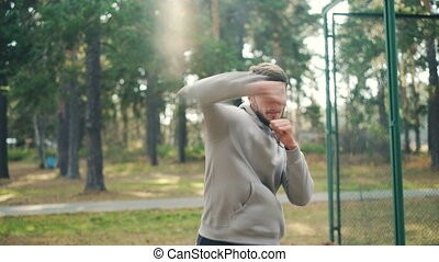 Professional sportsman is boxing alone in park moving arms...