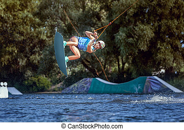 Professional sportswoman goes wakeboard ride.