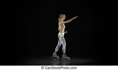 Professional sportswoman is performing exercises in a kangoo...
