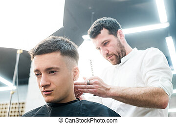 Professional styling. Close up side view of young man getting haircut by hairdresser with electric razor at barbershop
