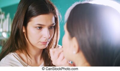 Professional stylist female doing make-up for young woman in front of mirror in beauty salon
