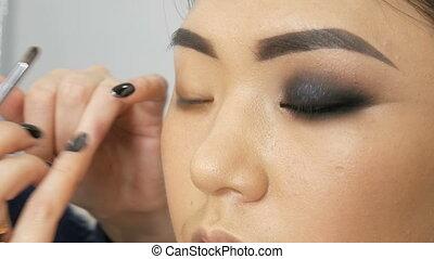 Professional stylist make-up artist makes up the smoky eye...